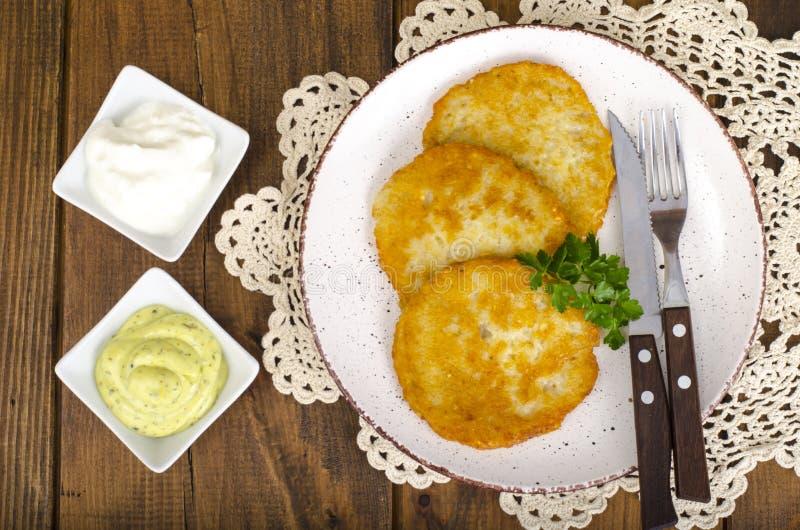 菜rosti、金黄油煎的土豆薄烤饼与垂度从花椰菜和酸性稀奶油 图库摄影