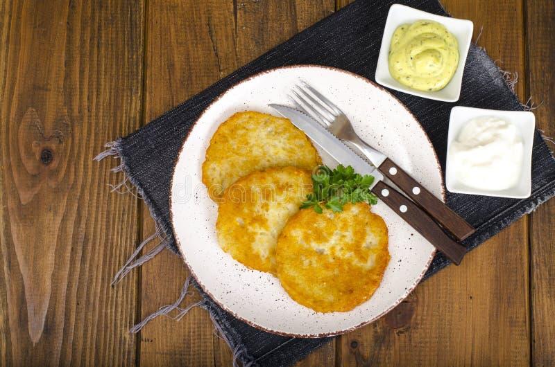 菜rosti、金黄油煎的土豆薄烤饼与垂度从花椰菜和酸性稀奶油 库存图片