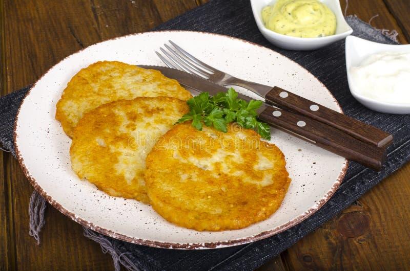 菜rosti、金黄油煎的土豆薄烤饼与垂度从花椰菜和酸性稀奶油 免版税库存图片