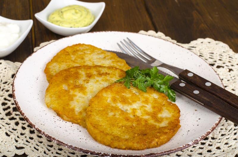 菜rosti、金黄油煎的土豆薄烤饼与垂度从花椰菜和酸性稀奶油 库存照片