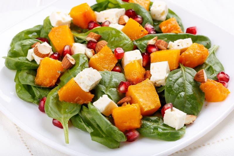 菠菜叶子、被烘烤的南瓜和希腊白软干酪沙拉用杏仁和石榴种子 库存照片