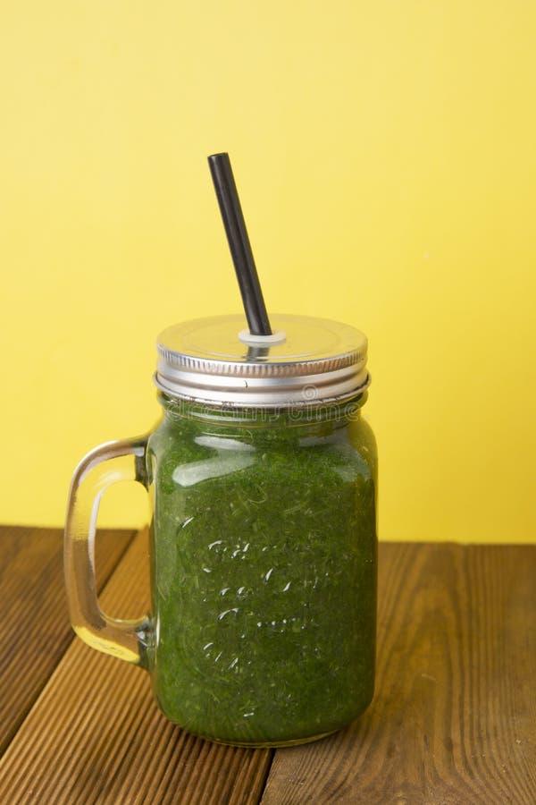 菠菜圆滑的人用绿色苹果 健康圆滑的人 木土气桌有黄色背景 库存图片