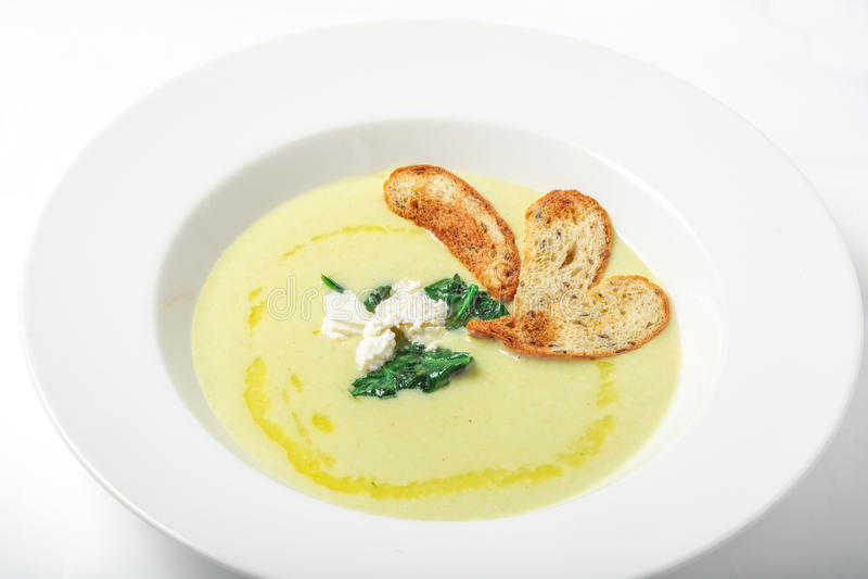 菠菜奶油色汤用乳酪和油煎方型小面包片在白色板材 免版税库存照片