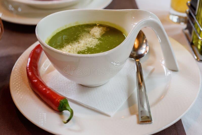 菠菜奶油色汤用在一个白色碗的辣椒 免版税图库摄影