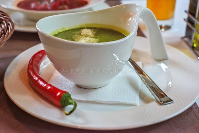 菠菜奶油色汤用在一个白色碗的辣椒 免版税库存照片