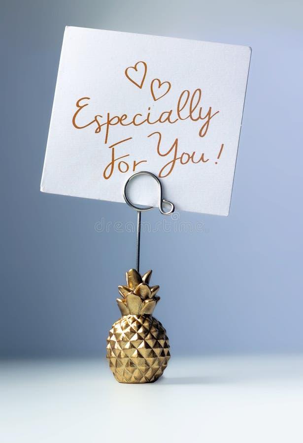 菠萝与题字的纸持有人-特别是您的,蓝色被设色的背景的 免版税库存图片