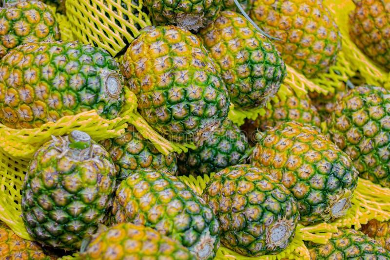 菠萝在市场上对顾客的待售 菠萝背景 库存图片