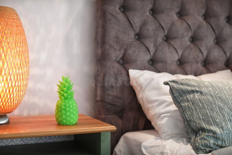 菠萝塑造了蜡烛和灯在床头柜上 免版税图库摄影