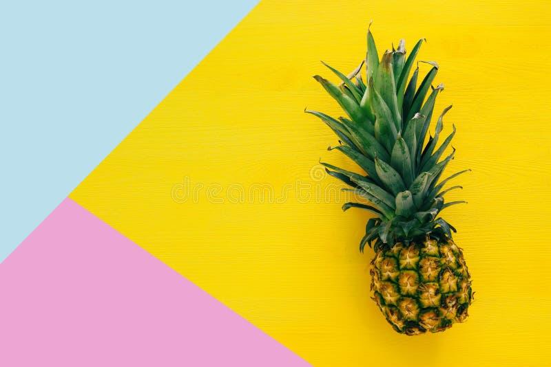菠萝顶视图在五颜六色的桌上的 夏天和热带概念 免版税库存照片