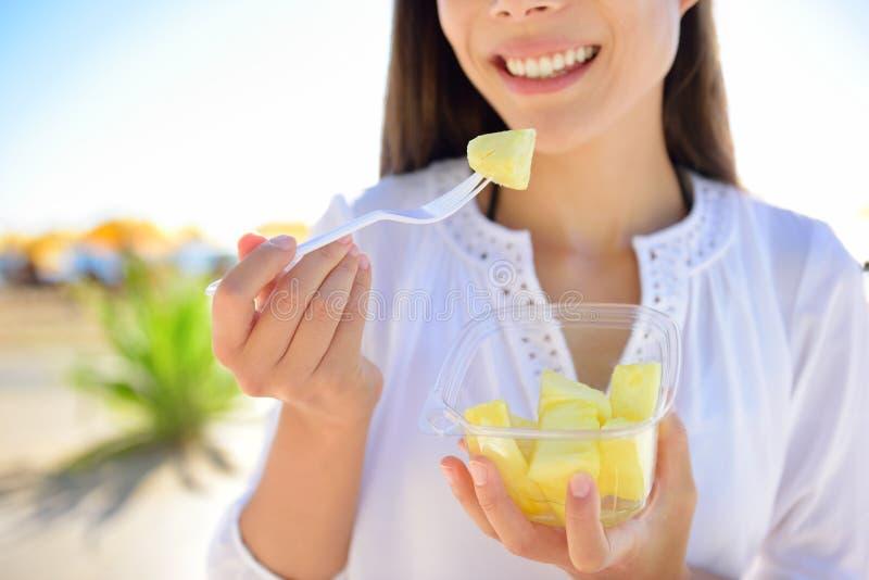 菠萝-吃切的夏威夷果子的妇女 图库摄影