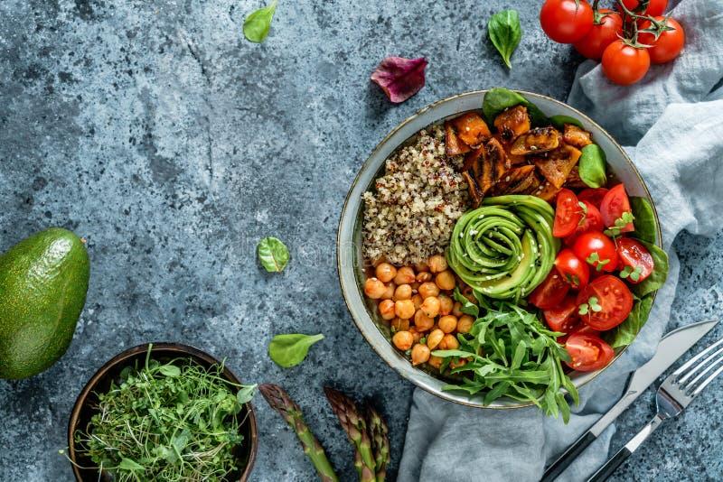菩萨与被烘烤的地瓜,鸡豆,奎奴亚藜,蕃茄,芝麻菜,鲕梨,在浅兰的背景的新芽的碗沙拉 免版税库存照片