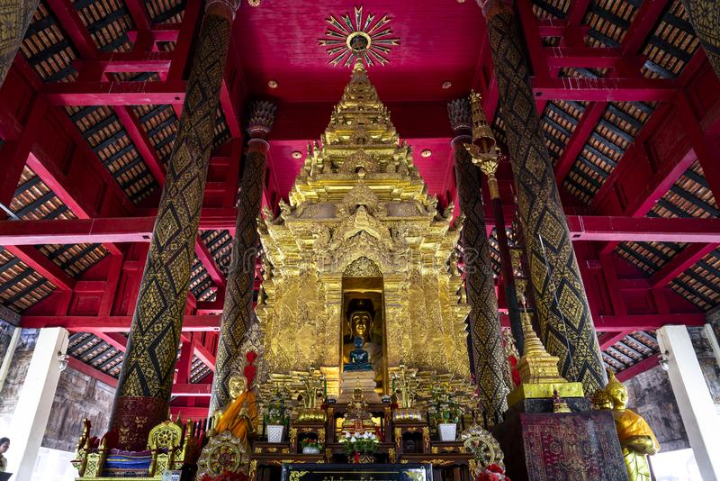 菩萨图象在Wat Prathat Lampang Luang,古老佛教寺庙主要大厅的金黄塔在Lampang,泰国 免版税图库摄影