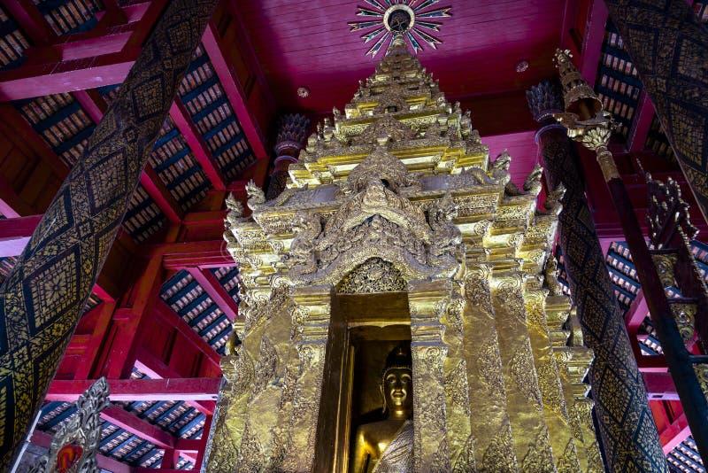 菩萨图象特写镜头在Wat Prathat Lampang Luang,古老佛教寺庙主要大厅的金黄塔在Lampang 图库摄影