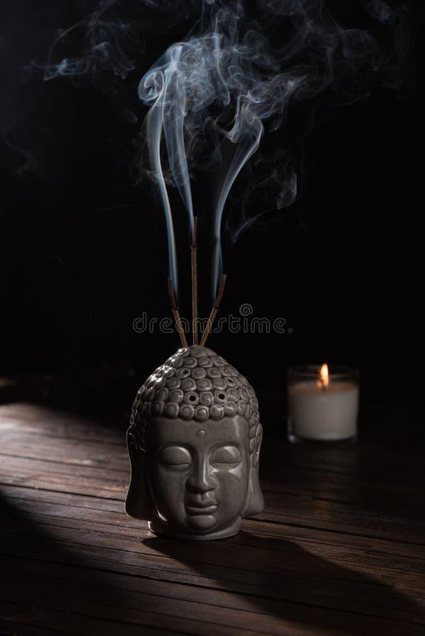 菩萨头雕塑用灼烧的香火棍子和蜡烛 免版税库存照片