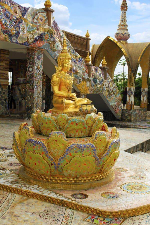 菩萨阁下金黄坐的雕象,坐在莲花,装饰用美丽,五颜六色的锦砖在酸碱度入口  库存照片