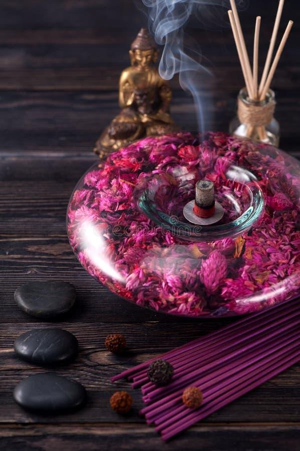 菩萨雕象、精油、香火棍子和石头按摩 免版税库存图片