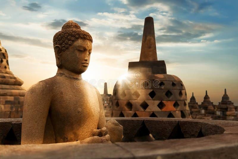 菩萨雕象以日出为背景的在婆罗浮屠寺庙  Java海岛 印度尼西亚 免版税库存照片