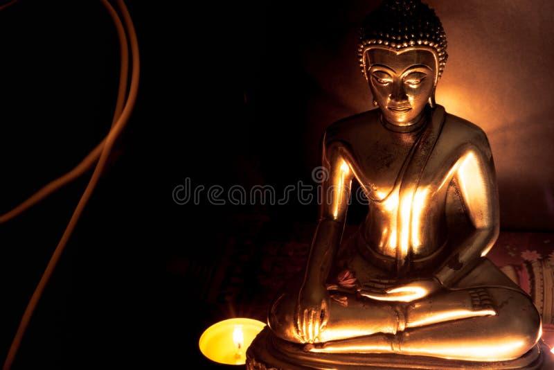 菩萨雕象选择聚焦与被弄脏的灼烧的蜡烛lig的 库存照片