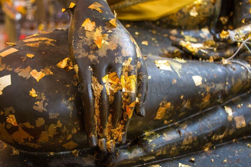 菩萨雕象黑表面关闭的手在古庙 免版税图库摄影