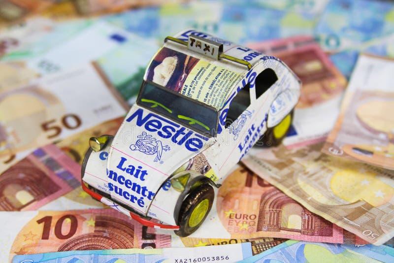 菲尔森,德国- 5月20 2019年:每年车汽车费用概念-汽车模型由被回收的罐头制成在欧元纸币银行 免版税库存照片