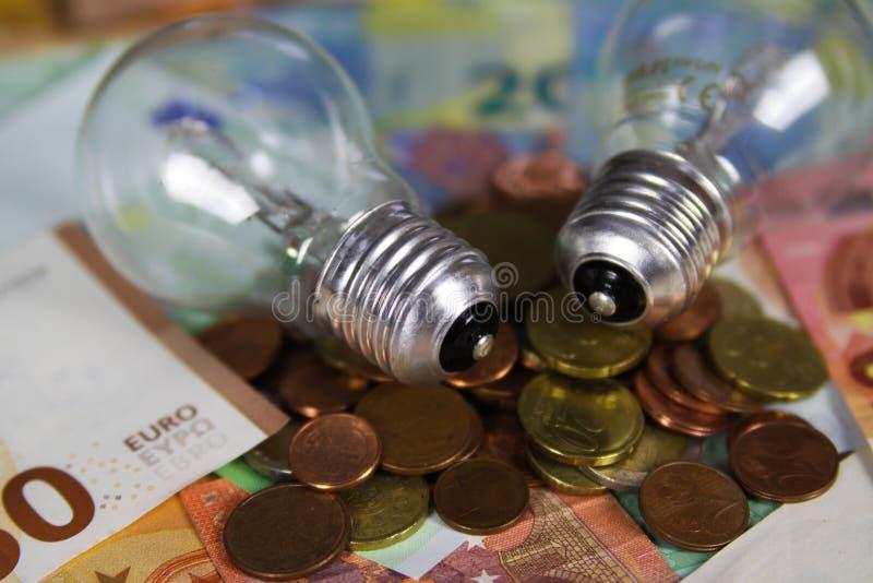 菲尔森,德国- 5月20 2019年:电源费用概念-在欧元纸币钞票和堆的电灯电灯泡硬币 图库摄影