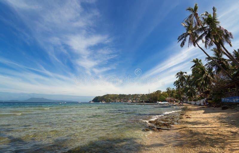 菲律宾加莱拉港萨邦白沙滩上的海、蓝天、棕榈和船只 热门旅游和潜水点 库存照片