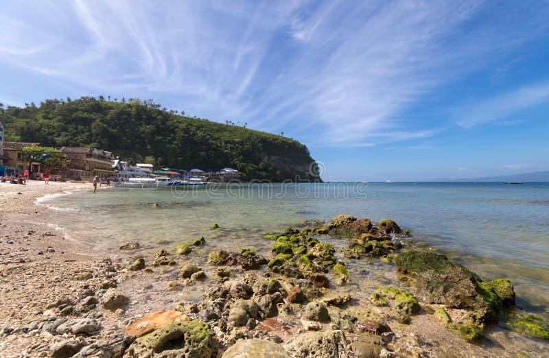 菲律宾加莱拉港萨邦白沙滩上的海、蓝天、棕榈和船只 热门旅游和潜水点 图库摄影