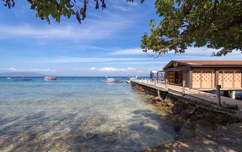 菲律宾加莱拉港萨邦白沙滩上的海、蓝天、棕榈树、平房和船只 热门旅游和潜水点 免版税库存图片