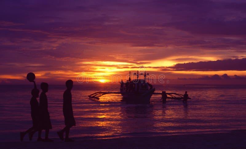 菲律宾海岛:日落的三个男孩在博拉凯 免版税库存图片