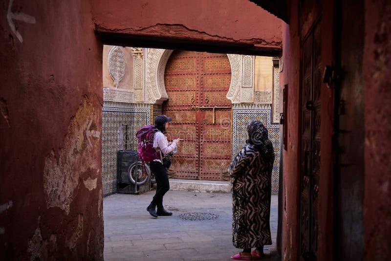 菲斯,摩洛哥- 2018年12月07日:在一个背包徒步旅行者游人和一个地方老妇人之间的对比在菲斯麦地那  免版税图库摄影