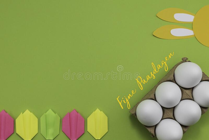 """菲涅·帕斯达根,荷兰语中的""""复活节快乐"""",带有鸡蛋、兔耳和花 图库摄影"""