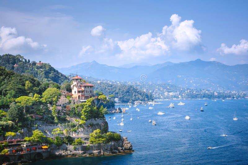 菲诺港,利古里亚,意大利- 2018年8月09日:美好的空中白天视图从上面到在水的小船,五颜六色的房子,山 图库摄影