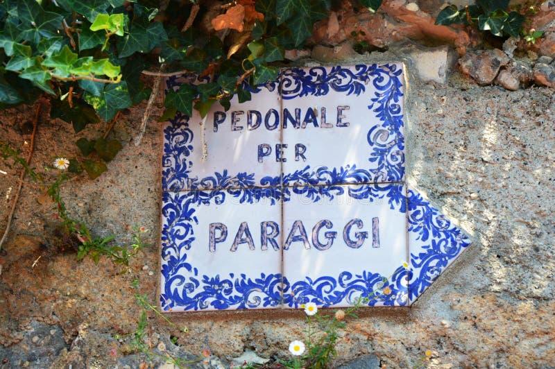 菲诺港,意大利- 2017年6月13日:陶瓷标志Pedonale每Paraggi,在峭壁的走的足迹从Paraggi的菲诺港 图库摄影