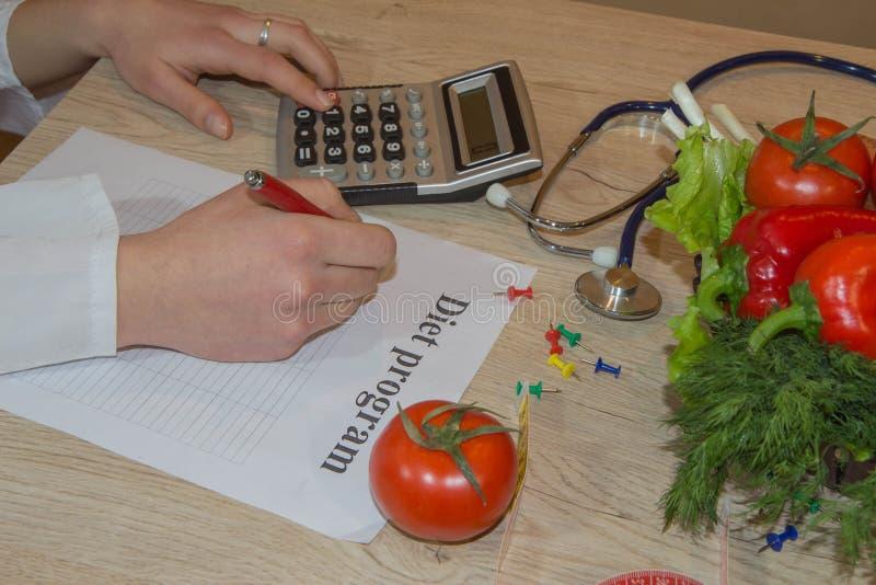 营养师医生文字在桌上的饮食计划 做健康吃菜单的无法认出的营养师 库存照片