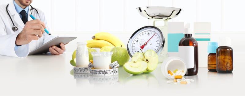 营养师营养师医生规定坐在书桌办公室的处方用苹果,酸奶,医疗药物,磁带米和 免版税图库摄影