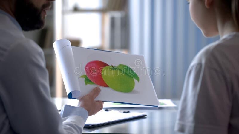 营养师谈话与关于健康食物的女孩,显示教育卡片 免版税库存图片