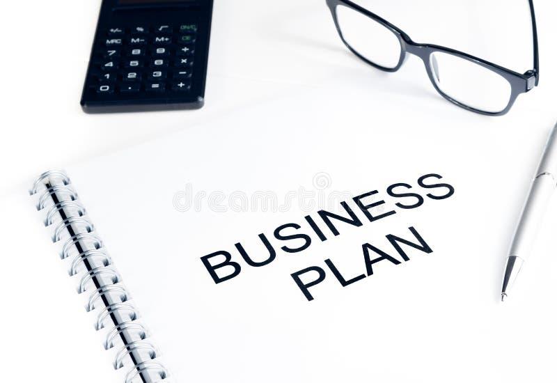 经营计划在计算器、玻璃和笔,企业概念附近措辞 免版税库存图片