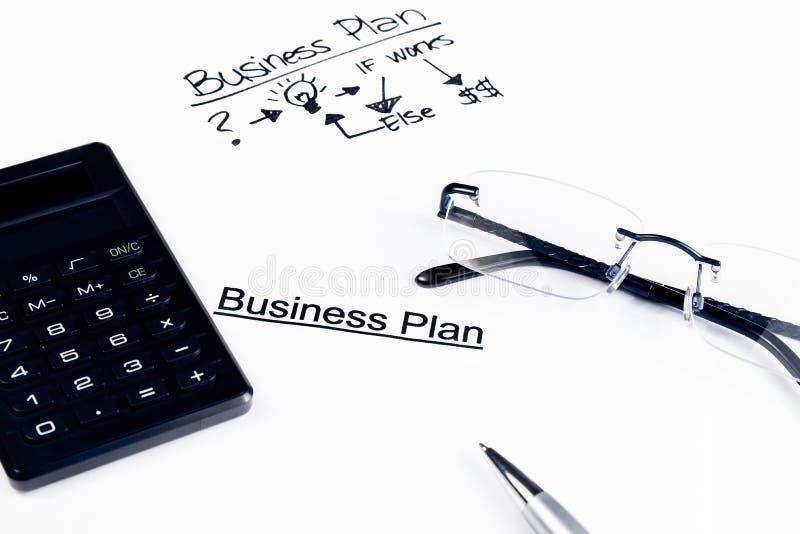 经营计划在玻璃、计算器和笔,企业概念附近措辞 免版税库存照片