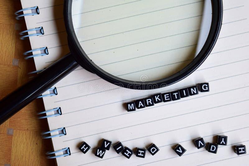 营销词的概念在木立方体的与书在背景中 库存图片