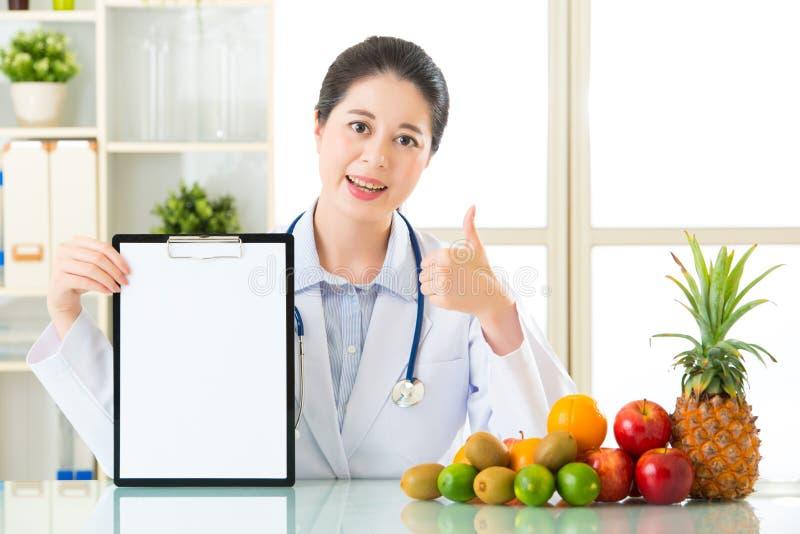 医治营养师用举行空白的剪贴板和thum的果子 库存照片