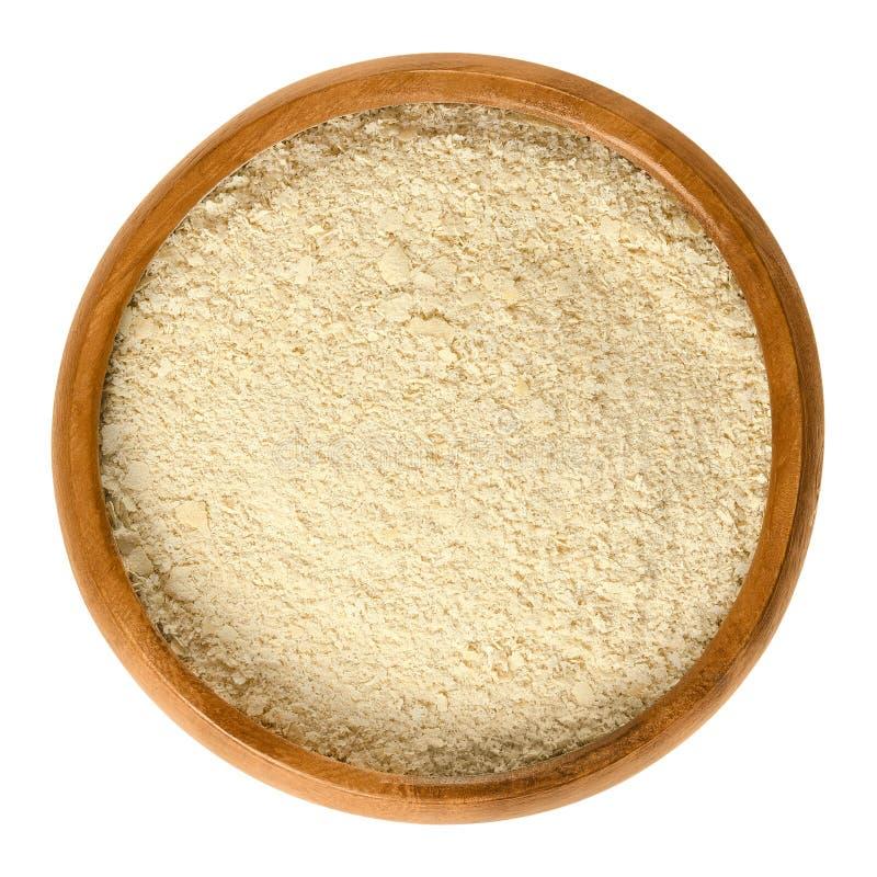 营养酵母在白色的木碗剥落 库存图片