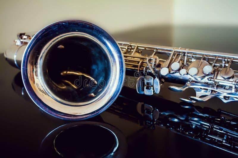 萨克斯管进程 木管乐器古典仪器 爵士乐,蓝色,经典之作 音乐 在黑背景的萨克斯管 黑镜子surfac 库存照片