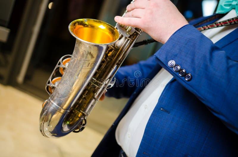 萨克管演奏员 弹萨克斯管的萨克斯管吹奏者手 女低音有爵士乐仪器特写镜头的萨克斯管演奏员 免版税库存图片