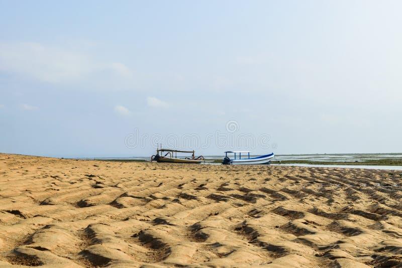 萨努尔海滩在印度洋的低潮时间在有两条小船的巴厘岛在背景中 免版税图库摄影