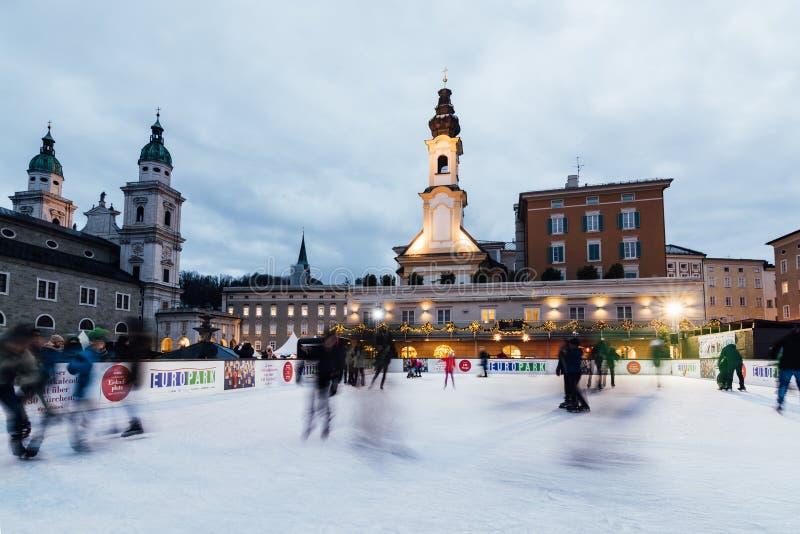 萨尔茨堡,奥地利- 2018年12月:滑冰在滑冰场的人们在老镇圣诞节市场上 图库摄影