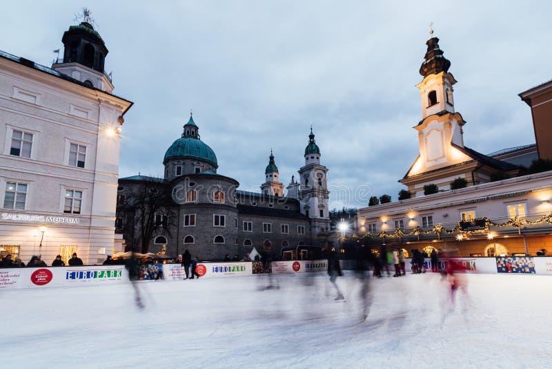 萨尔茨堡,奥地利- 2018年12月:滑冰在滑冰场的人们在老镇圣诞节市场上 免版税库存图片