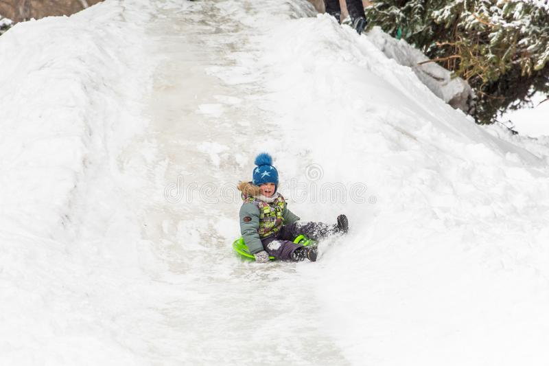萨拉托夫/俄罗斯- 2018年3月8日:与冰幻灯片的儿童乘驾 背景海滩异乎寻常的做的海洋沙子雪人热带假期白色冬天 室外的活动 冬日在城市公园 库存照片