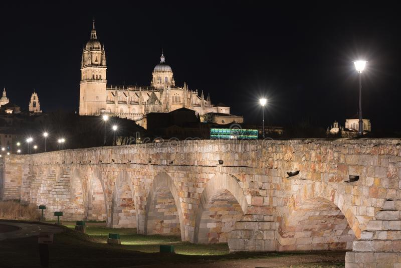 萨拉曼卡大教堂和罗马桥梁夜视图在Tormes河,萨拉曼卡,西班牙 库存图片
