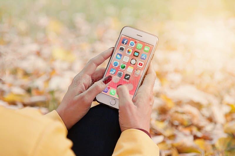 萨拉热窝,波斯尼亚黑塞哥维那- 2018年10月15日:妇女有普遍的应用程序象的藏品智能手机在10月15日屏幕上,i 库存图片