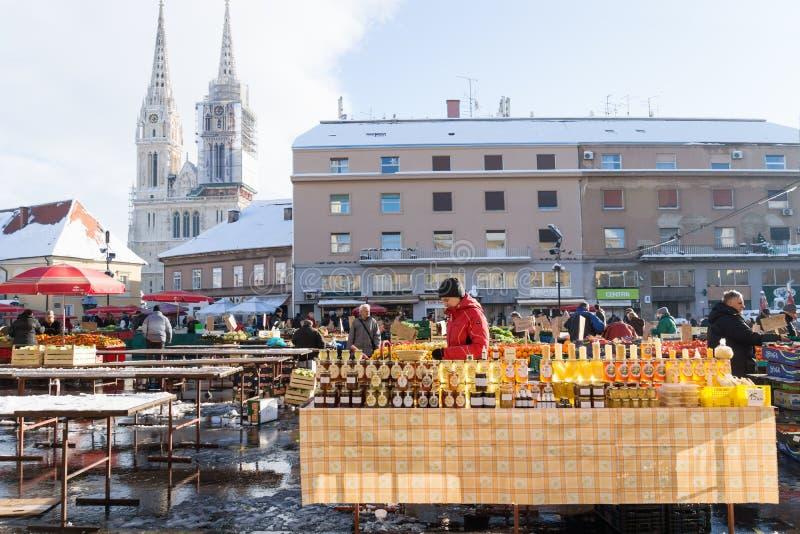 萨格勒布,克罗地亚:2016年1月7日:与蜂蜜玻璃的立场在冬天期间的Dolac市场上与与大教堂的雪后面的 库存图片